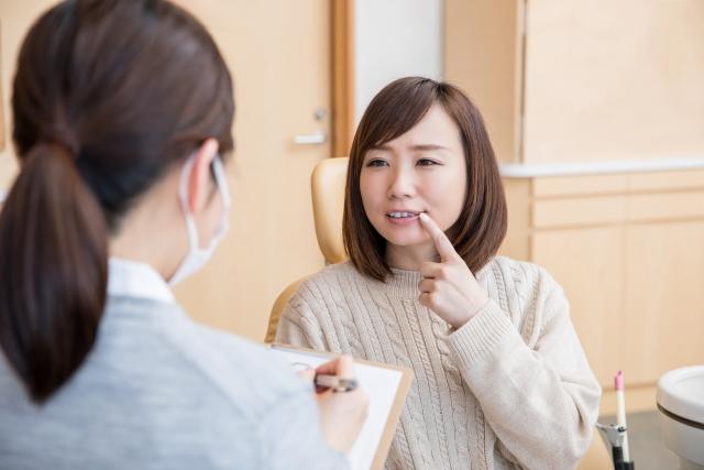 歯医者で問診を受ける女性
